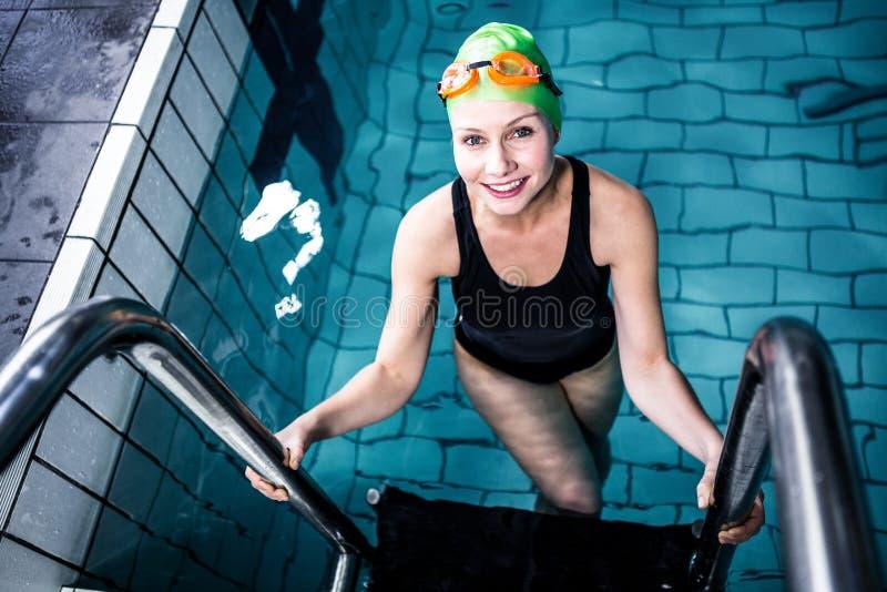 Glimlachende zwemmersvrouw die van het zwembad weggaan royalty-vrije stock afbeelding