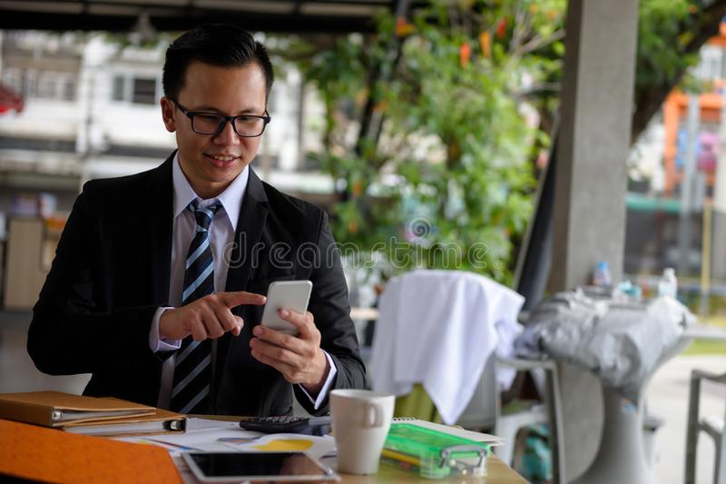 Glimlachzakenman met smartphone in koffiewinkel royalty-vrije stock foto