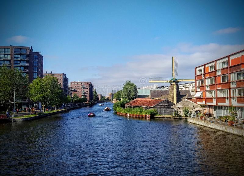 Glimpse of Amsterdam. River, amstel, xity, city, capital, netherlands, water, windmill, urban, modern, architecture, details, sky, summer, travel, vacation royalty free stock photography
