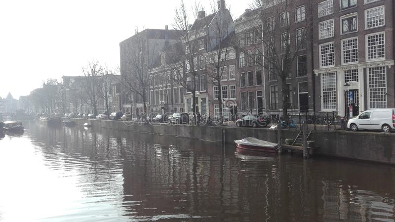 Glimpse of amsterdam river, on a cold and gray autumn day. the boats rest still and sleepy along the canal and everything seems to. Have stopped and fallen stock images