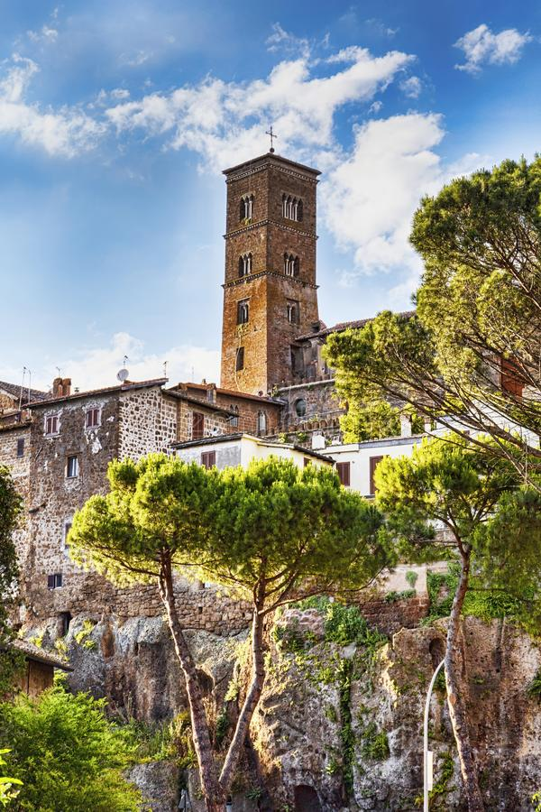 A glimpse of the ancient village of Sutri and the bell tower. A glimpse of the medieval village of Sutri and the bell tower of Holy Mary Assumption s Co stock photo