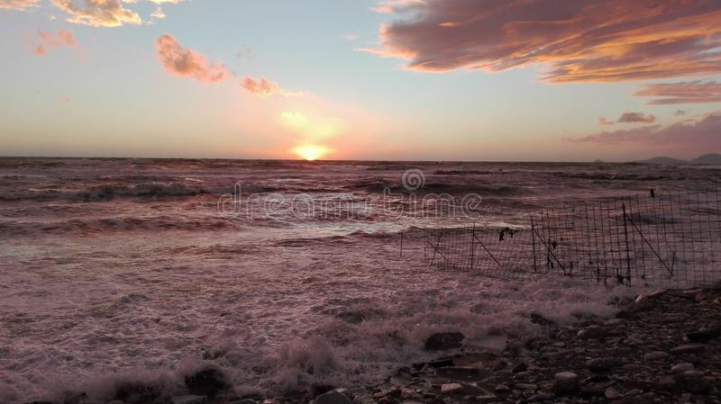 A glimpse of the beach at sunset, a magical moment in which everything is colored with bright colors. the clouds frame the. Maritime landscape and the sun stock images