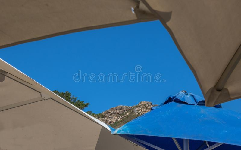 A glimpse of blue sky its summer break. A glimpse of deep blue sky and the cliffs of a mountain through a gap from below large umbrellas image with copy space in stock images