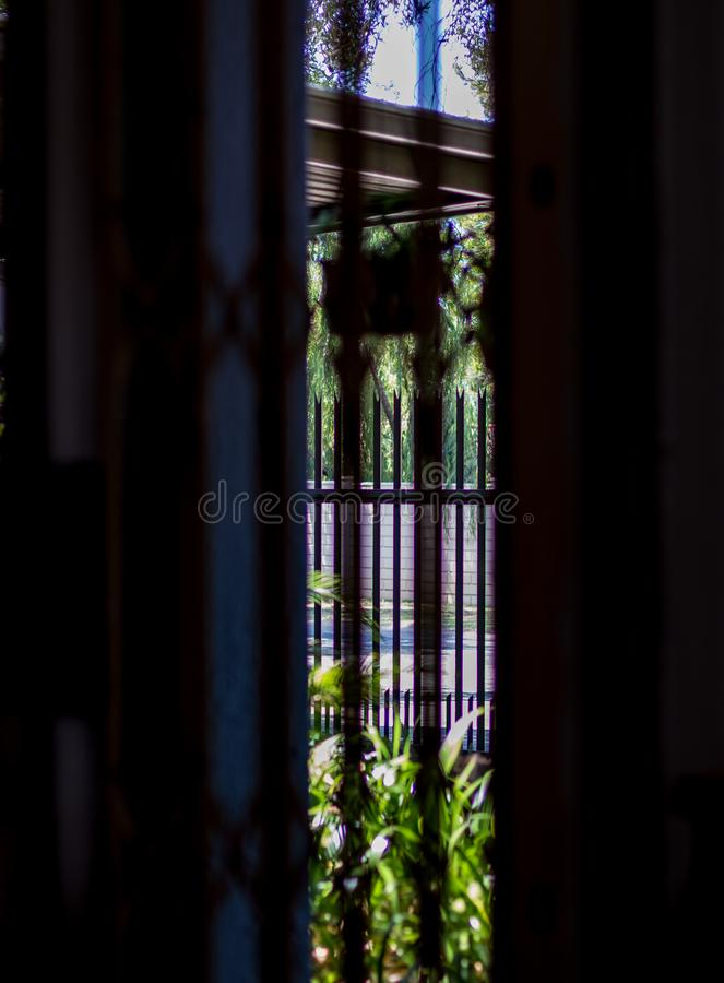 A glimpse of the outside - concept freedom. A glimpse of the outdoors through bars in a gap in a high wall image in portrait format stock photography