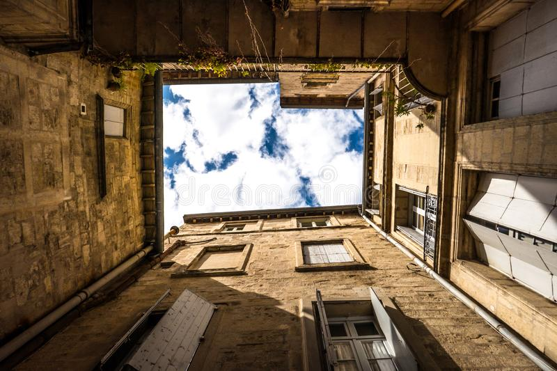 Glimpse of sky from a courtyard. Glimpse of sky seen from a square courtyard of a building in a city in the south of France stock photos
