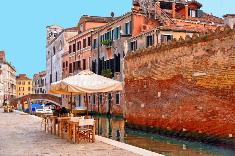 Glimpse of Venice with one of its canals with boats, historic buildings and people drink and relax in outdoor table and chairs of stock images