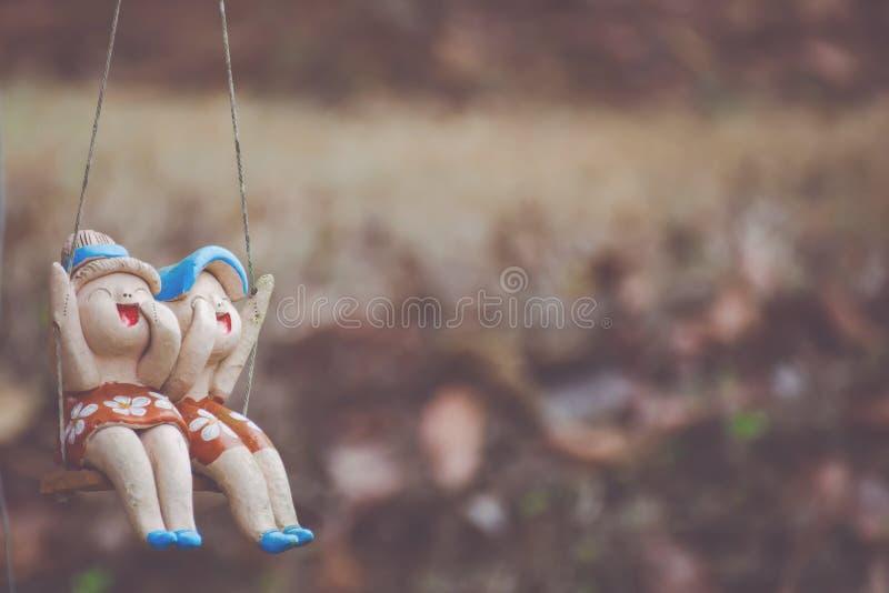 Gliniane dziecko lale siedzi na huśtawkach w domu, pojęcie dekoracja obrazy royalty free