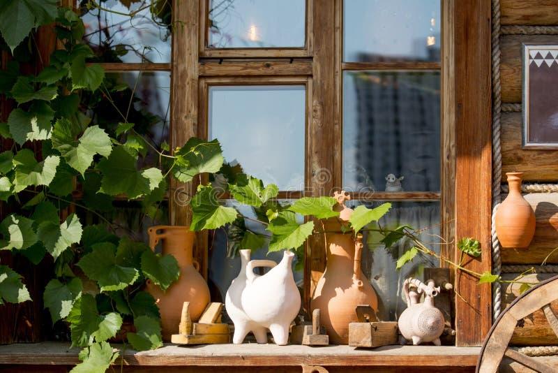 Gliniany brąz puszkuje przed okno drewniany dom fotografia royalty free