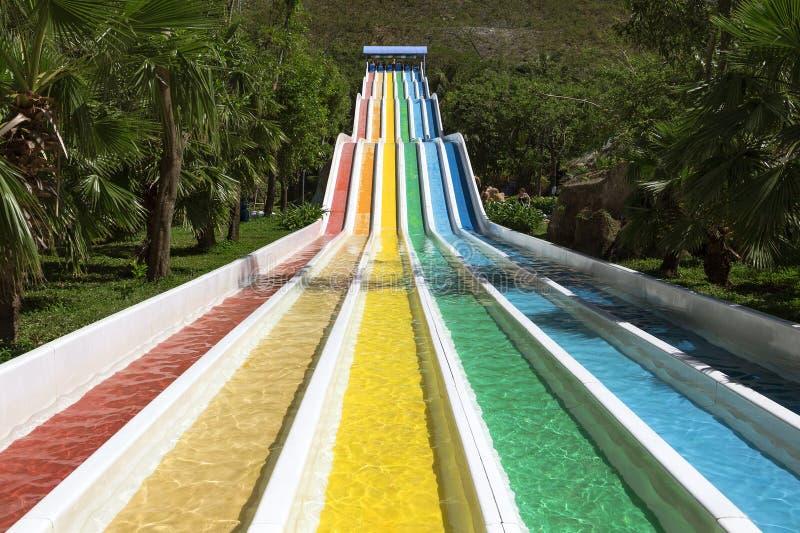 Glissière d'eau avec les voies colorées lumineuses dans la bordure de parc d'aqua photos stock