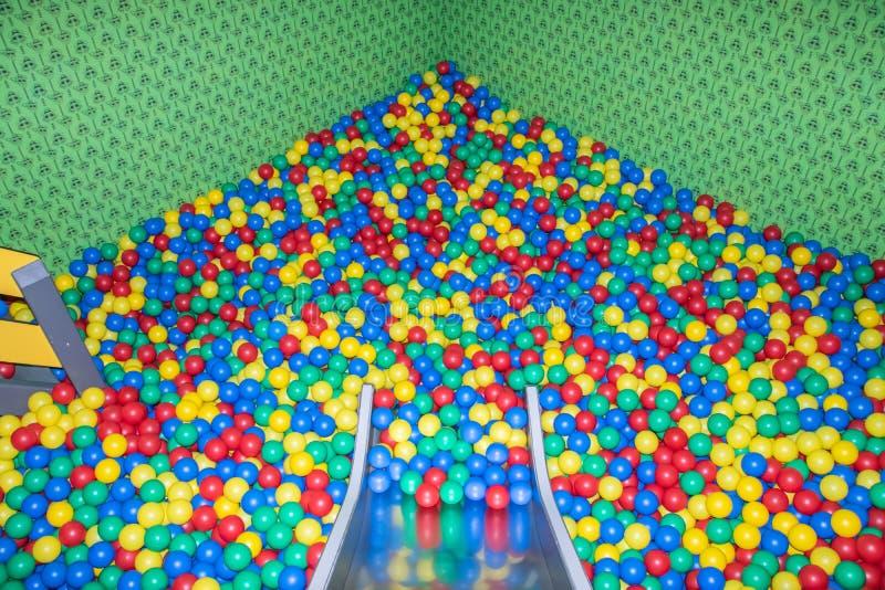 Glissi?re de b?b? en m?tal descendant ? la piscine avec beaucoup de boules color?es dans les enfants jouant la pi?ce photos stock
