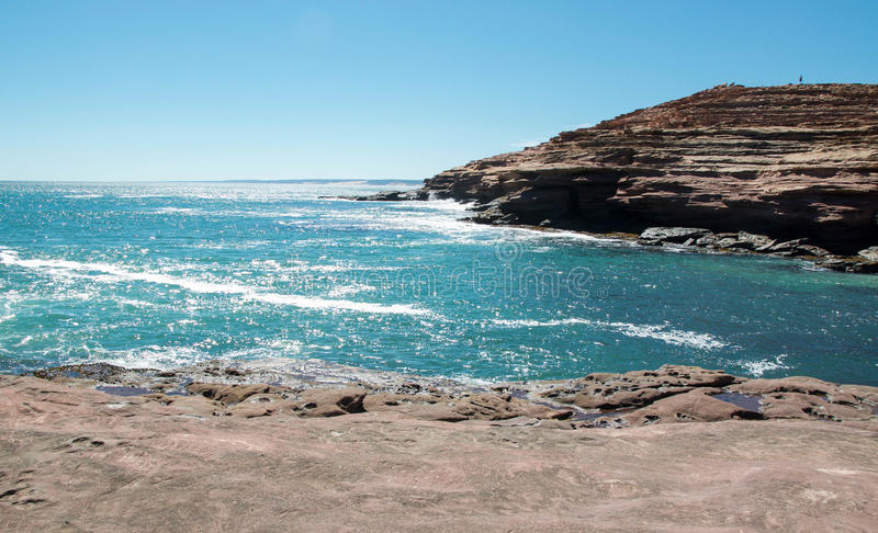 Glistening Ocean at Pot Alley. Glistening Indian Ocean waters and Layered sandstone cliffs at the Pot Alley cove under clear blue skies in Kalbarri, Western stock photo