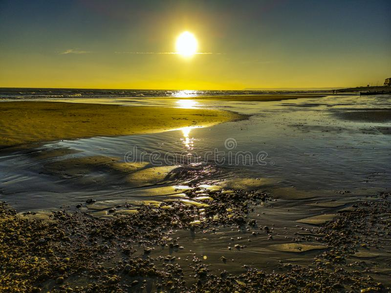 Low Tide sunset at Bexhill, East Sussex, England. The glistening sand and evening sun make for a beautiful poster or print for home or office decor usage stock image