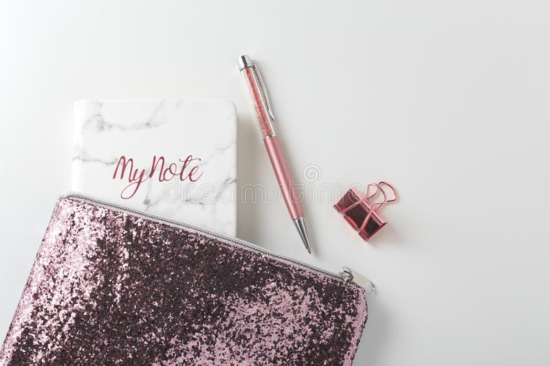 Glitter bag with pen and planner on white desk stock photo