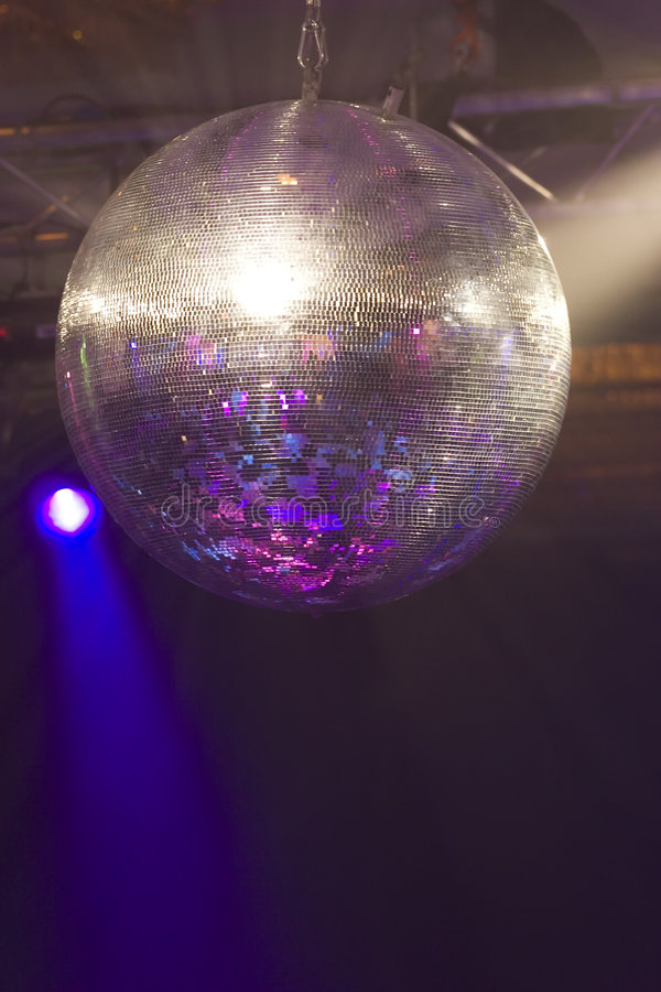 Glitter Ball. A huge mirrored glitter ball illuminated by coloured lights royalty free stock image
