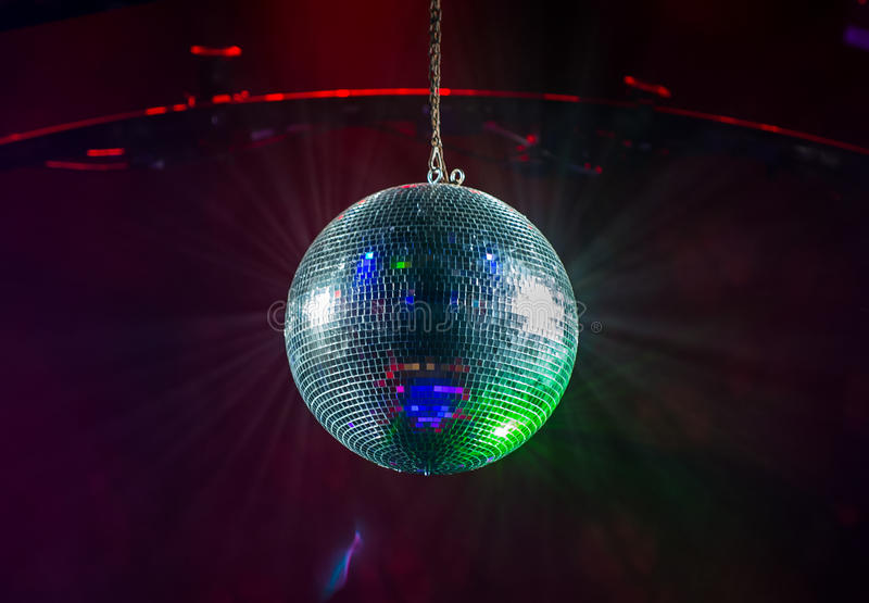 Glitter ball. A colourful glitter ball hanging from the ceiling will lights shining stock images
