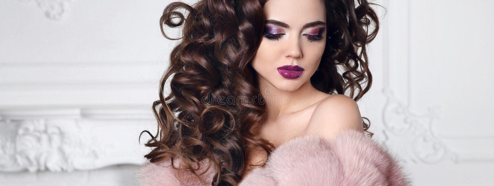 Glitter beauty makeup. Brunette with curly hair style wears in p. Ink fur coat. Glossy lipstick and purple eye shadow make-up royalty free stock image