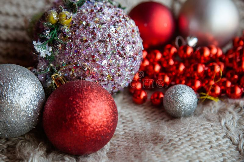 Glitter christmas ball bead knit red silver decor. Shiny glittery christmas balls selection. red and silver baubles bead string on the knit textured fabric. new stock images