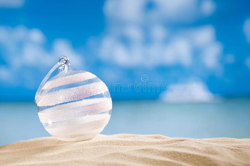 Glitter christmas glass ball on beach with seascape. Glitter christmas glass ball on beach with ocean seascape background stock images