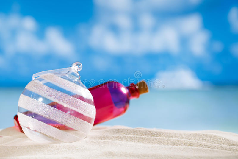 Glitter christmas glass ball and bottle on beach with seascape. Background stock photos