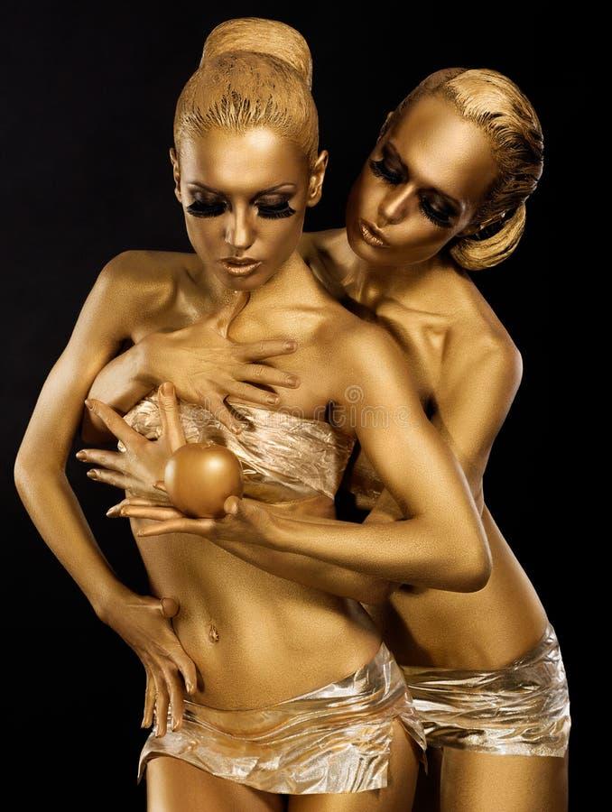 Glitter. Glaze. Seductive Women with Golden Bodies Hugging. Fantasy. Women with Golden Bodies Hugging. Fantasy royalty free stock images