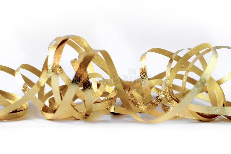 Glitter gold ribbon tape curl isolated on white. Brilliance concept stock photo