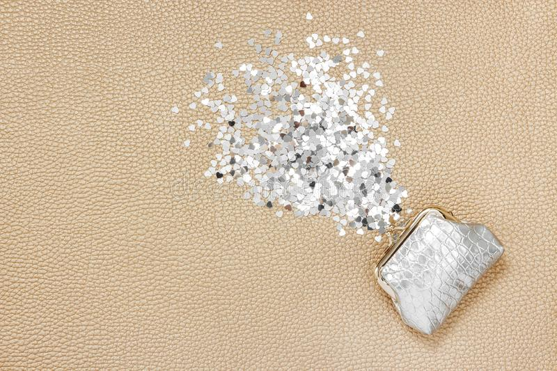 Glitter hearts pouring out of a silver purse stock photography