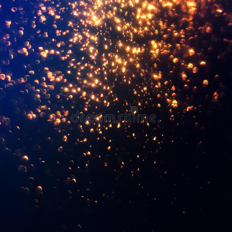 Glitter lights abstract background. Golden Sparkle stardust on b. Lue and black defocused texture stock photography