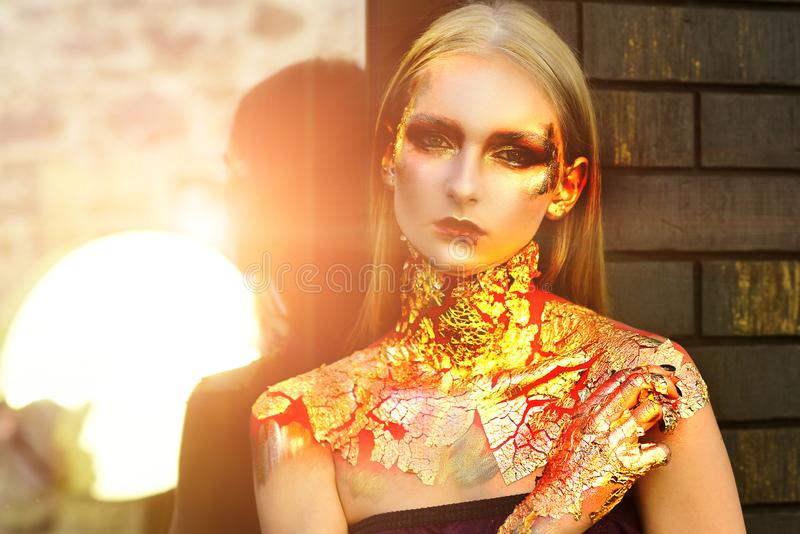 Glitter metallic shine golden make-up. Vampire woman with bloody lips and golden eyes. Halloween Witch with red bloody stock photo