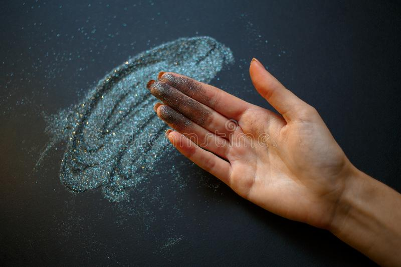 Glitter on their hands. Glitter texture christmas abstract background. Colored sparkle background. stock photo