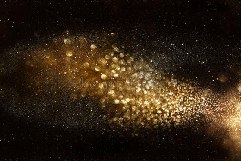 glitter vintage lights background. dark gold and black stock image