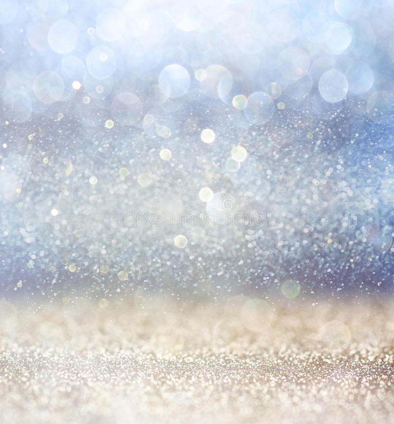 Glitter vintage lights background with light burst . silver, blue and white. de-focused. Glitter vintage lights background with light burst . silver, blue and stock photos