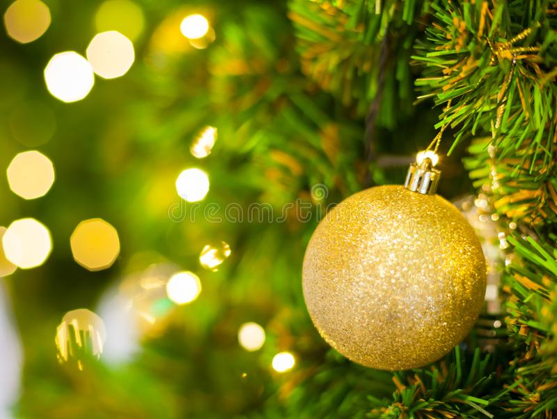 Glittering Baubles with Glowing Sparkling Gold defocused Light bokeh Illumination background with decorated Christmas Tree. royalty free stock photos