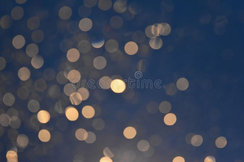 Glittering bokeh circular gold on blue background. stock images