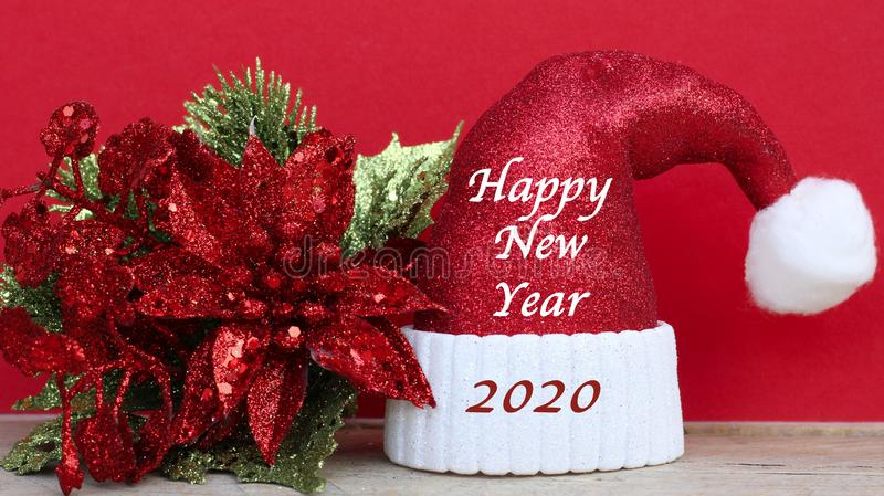 Happy new year 2020 message on a sparkling santa claus hat on a red background stock photo