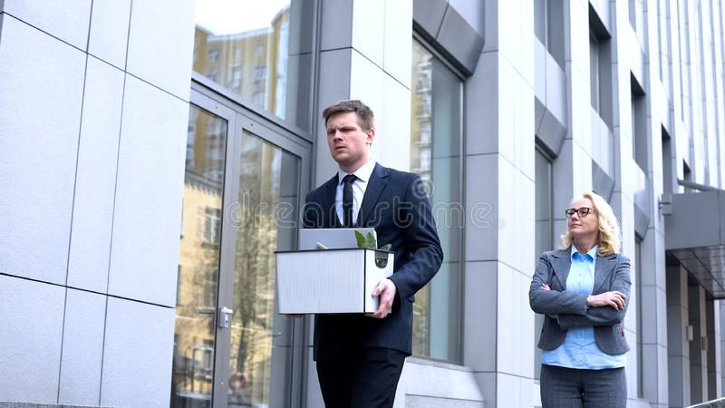Gloating mature woman looking at dismissed young worker leaving office, conflict stock images