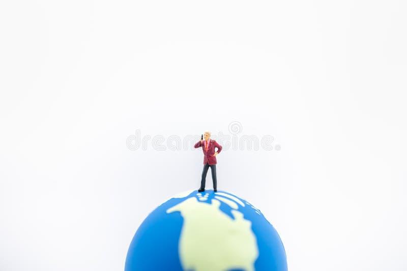 Globaal Tecnology-Zaken en Communicatie concept Sluit omhoog van zakenman miniatuurcijfer die en maak vraag met mobiel bevinden z royalty-vrije stock foto