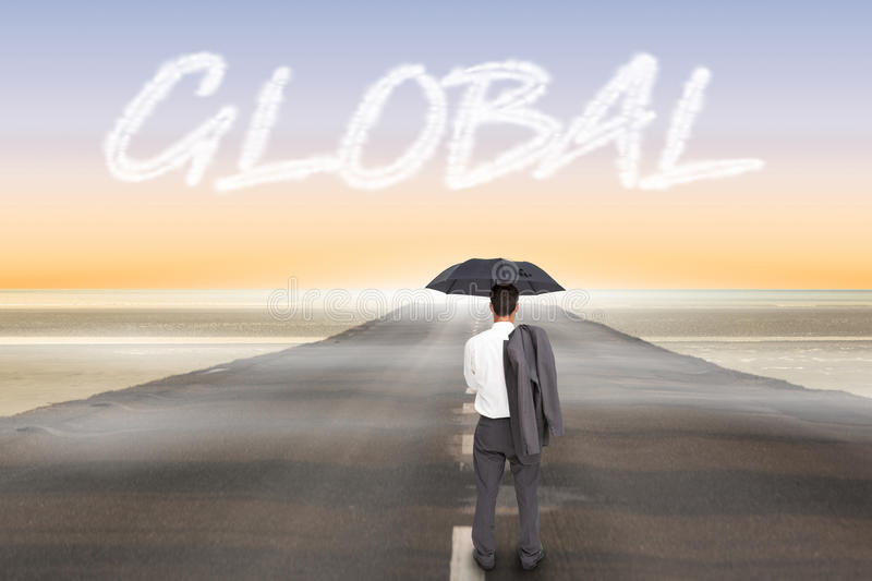 Global against road leading out to the horizon. The word global and businessman standing back to camera holding umbrella and jacket on shoulder against road royalty free stock image