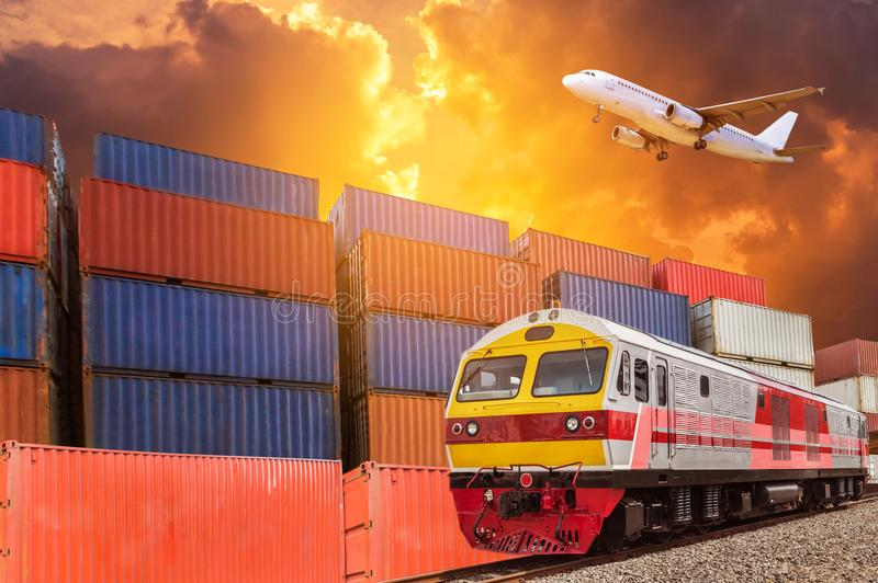 Global business with commercial cargo freight train and container cargo stack at the dock during cargo plane flying above on sunse stock photo