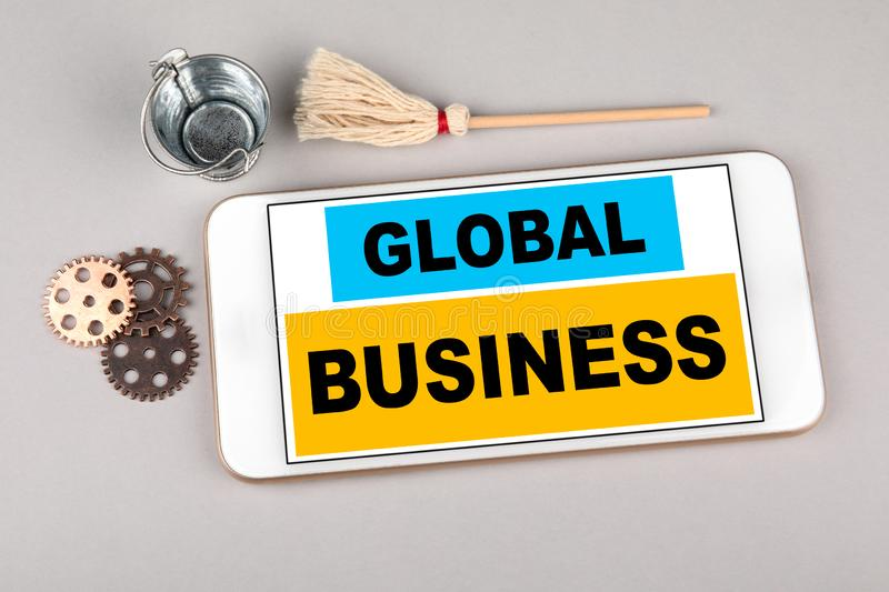 Global Business concept. Mobile phone on gray table royalty free stock photo