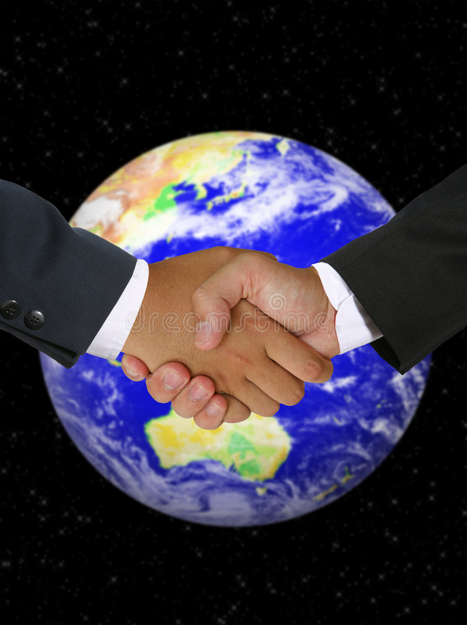 Global Business Deal. Men shaking hands in a global business deal royalty free stock photo
