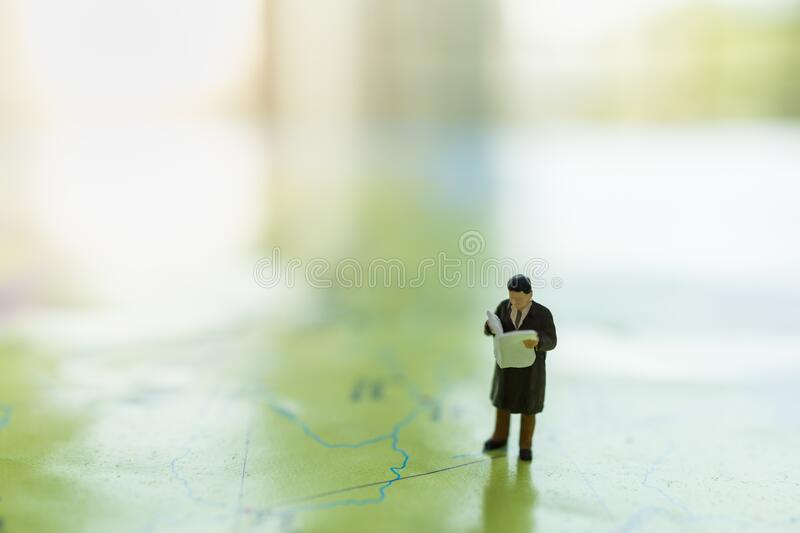 Global Business and Planning Concept. Close up of businessman miniature figure standing and reading newspaper on world map with. Copy space royalty free stock photos