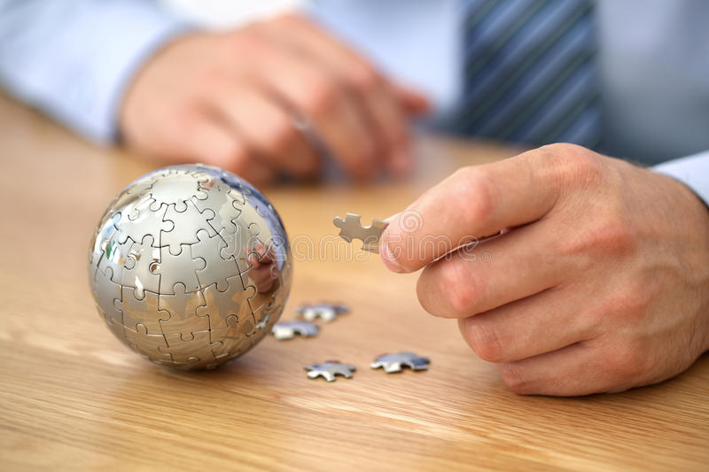 Global business strategy. Businessman solving globe puzzle concept for business solutions and strategy royalty free stock images