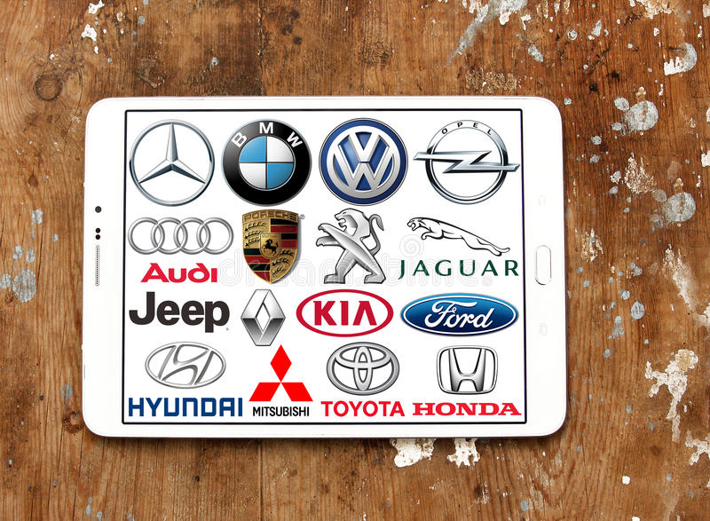 Global car brands and logos. Collection of the famous car brands logos on white tablet on wooden background. Brands like mercedes , volkswagen , bmw , toyota stock images