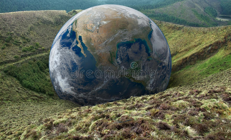 Global downfall. Terrestrial globe on hilly overgrown ground royalty free stock photography
