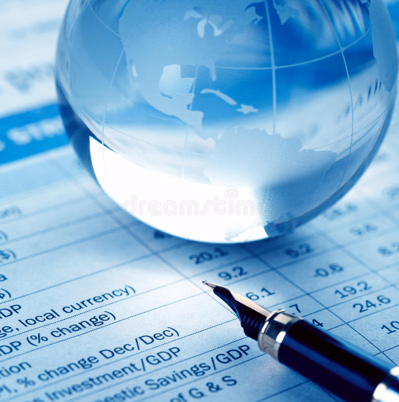 Global Economy. A glass world globe resting on a financial chart with a fountain pen indicating the world of finance