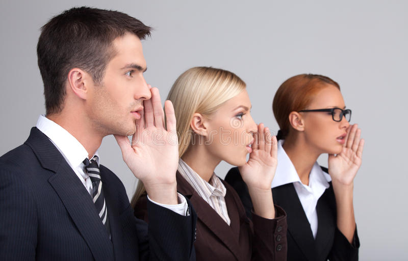 Global gossiping. Side view of three attractive young business p stock image