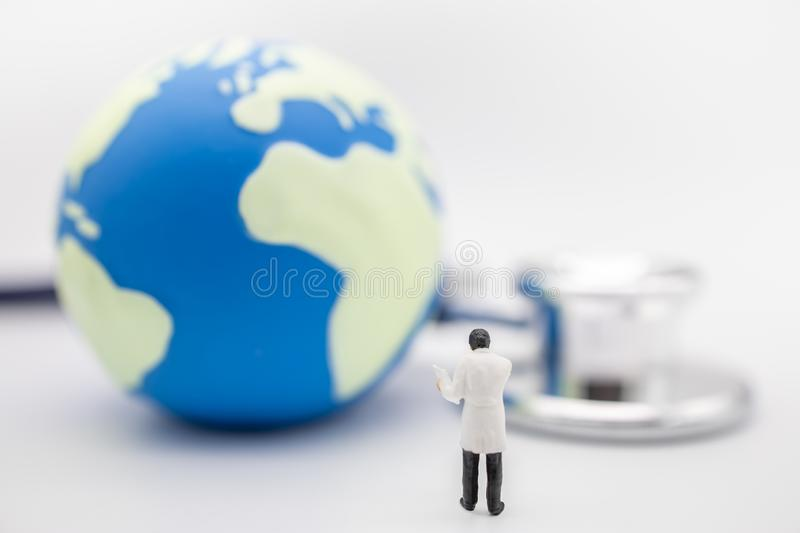 Global Health Care Concept. Close up of doctor miniature figure stanind with patient chart with mini world ball and Stethoscope. Global Health Care Concept royalty free stock photo