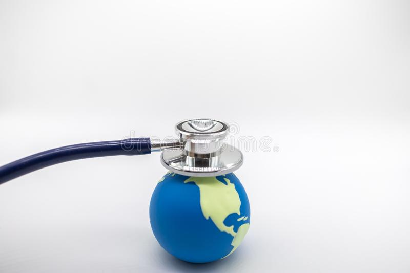Global Health Care, Environment Ecology, Earth Concept. Close up of doctor Stethoscope on mini world ball on white background and stock photography