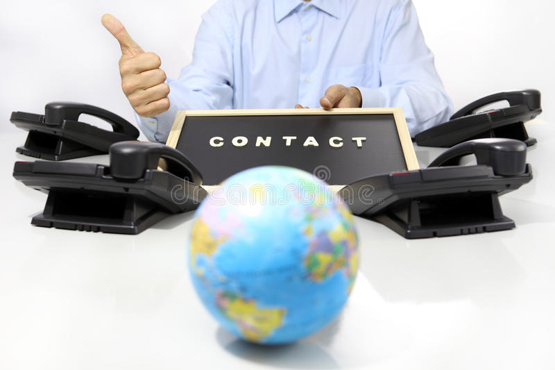 Global international contact concept, hand like with phon. Global international contact concept, hand like with office phone on desk and globe map stock photo
