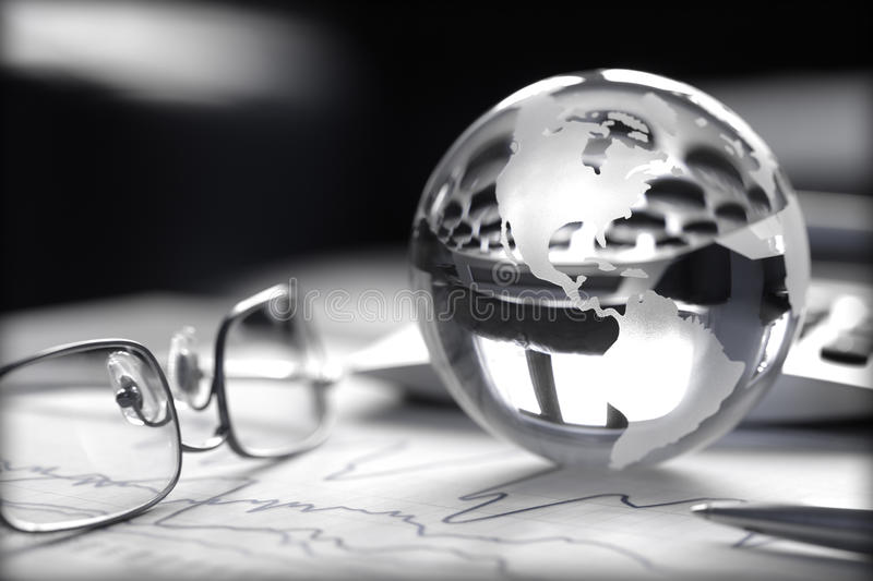 Global Investment. Toned image of glass globe with stock charts, calculator and spectacles stock photo